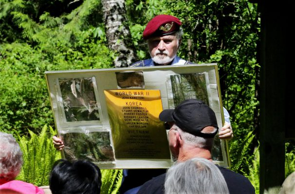 Bernie Moskowitz, class of 1957 and president of the Cleveland High Alumni Association, shows a display of names listed on brass along with photos of the forest to people gathered for the annual memorial to the fallen. (Alan Berner/The Seattle Times)