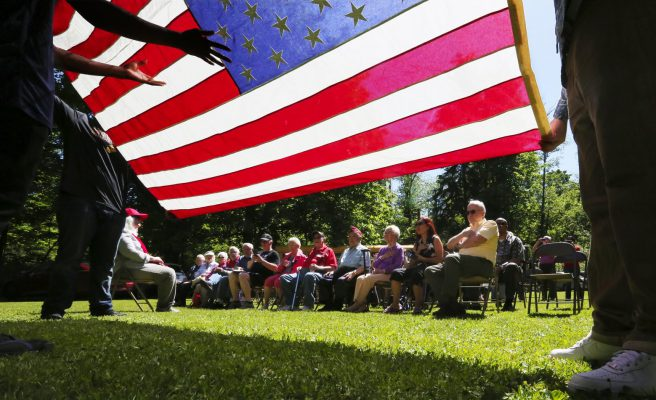 With the stars and stripes held by Cleveland High seniors, alumni and family gather Friday at the annual memorial for their fallen in war and to dedicate the new granite monument honoring them at the Cleveland High School Memorial Forest. (Alan Berner/The Seattle Times)