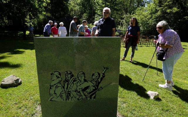 The back of the granite memorial has a depiction of four warriors. (Alan Berner/The Seattle Times)