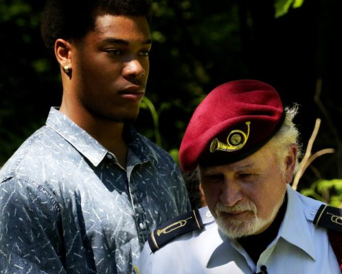 Cleveland High senior Jeffrey Beasley and Bernie Moskowitz, president of the alumni association, listen to speakers before the conclusion of the ceremony honoring fallen alums from the school. Beasley is planning on a career in the navy. (Alan Berner/The Seattle Times)