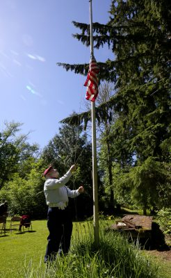 Before the memorial, Bernie Moskowitz lowers the flag to half-staff. (Alan Berner/The Seattle Times)