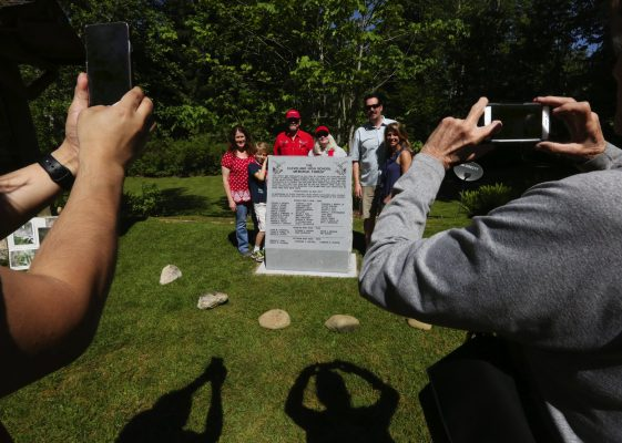 The Ronnie family gathers for a photograph at the new granite monument in the Cleveland High School Memorial Forest. Multiple generations of the family are alums of the school. (Alan Berner/The Seattle Times)